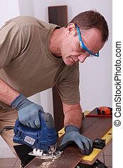 handyman drilling a hole through a board