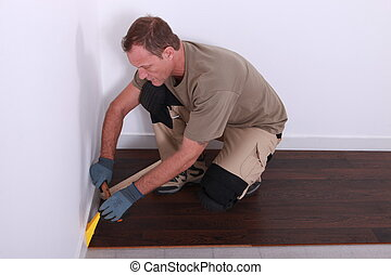 Workman installing laminate floor