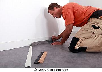 Man putting down linoleum on a baseboard