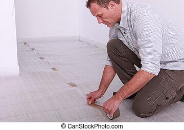 Man taping down underlay