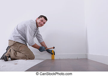 a man laying floorboards
