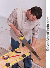 Man sawing laminate flooring