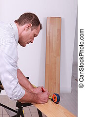 Tradesman marking a measurement on a wooden plank
