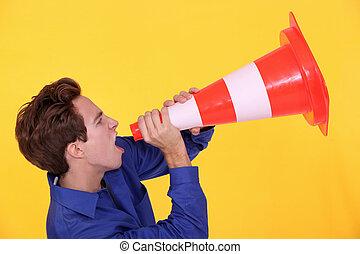 Man shouting through traffic cone