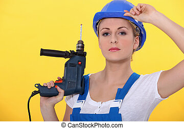 a blonde woman wearing an overall posing with a drill and adjusting her helmet