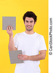craftsman holding two bathroom tiles