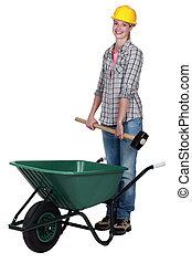 Tradeswoman placing a mallet in a wheelbarrow