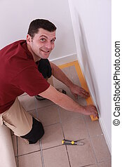 Man putting down tape around the edge of a tiled floor