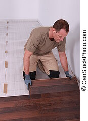 Handy-man laying wooden flooring
