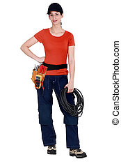 Handywoman holding cabling and wearing a tool belt