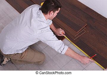 Man measuring wooden flooring