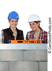 two craftswomen measuring a wall with a level