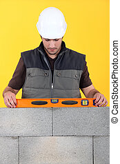 craftsman making measurements with level