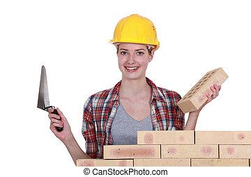 Female mason stood by wall
