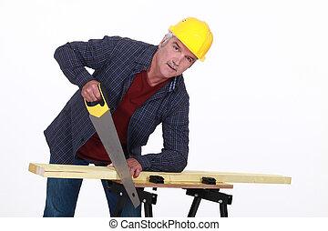 craftsman cutting a board with a saw