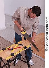 handyman cutting a board
