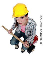 female builder holding a sledge hammer