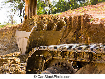 Back hoe standing in mining with raised bucket full of sand