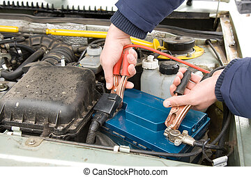 A mechanic using jumper cables to start a car battery