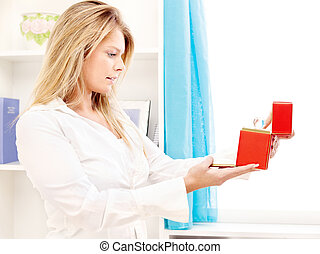 woman opening fancy box at home - Blond woman opening fancy...