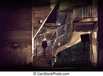 staircase in run down area - Man walking down staircase in...
