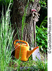 Garden tools - Yellow watering can, shovel and gloves by a...