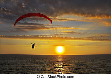The parachute above the sea on a sunset - Operated parachute...