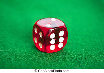 Single red dice on green background