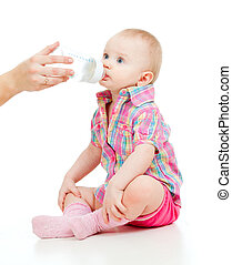 adorable child drinking from bottle. 10 months old girl.
