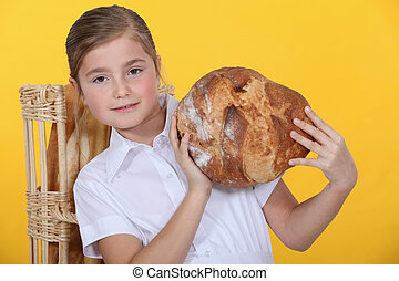 Proud young girl holding up a bread loaf