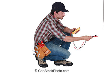 electrician crouching using tester