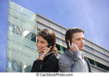 Montage of business couple in front of a modern building