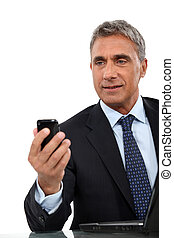 Director sending text message on phone