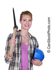 young female bricklayer posing with pickaxe and hard hat