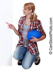 Kneeling tradeswoman pointing sideways