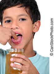 Boy tasting some honey