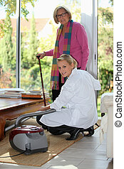 Young woman vacuuming for an elderly lady