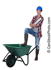 Tradeswoman with her foot propped on a wheelbarrow