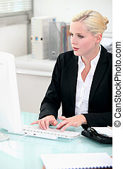 Blonde woman working at a desktop computer