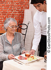 Young waiter serving lunch to an older customer