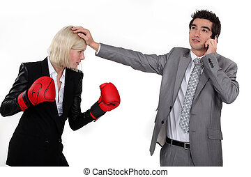 Businesswoman boxing a man on the phone