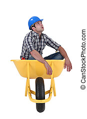 Foreman sitting in wheelbarrow isolated on white background