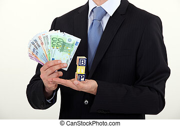 Man holding toy blocks and money