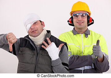 Healthy construction worker standing next to an injured man