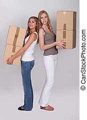 Young women carrying cardboard boxes