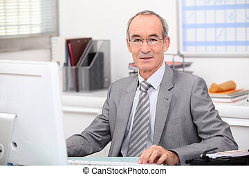 Senior businessman working at a computer