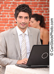 Young man alone using laptop