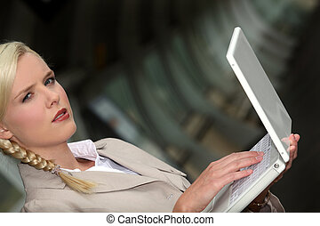 serious woman wearing a beige suit is working on her laptop...