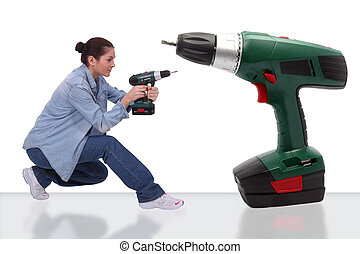 girl with bun holding drill near giant drill