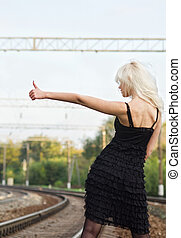 Sexy young girl is hitchhiking on a railroad. Rear view -...